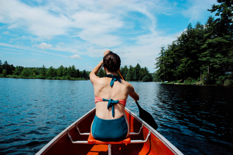 Women in a kayak canoe on a lake with trees